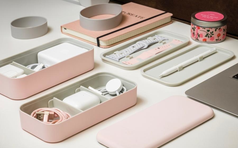 rectangle-shaped box with different layers in pink and different Apple products in each layer