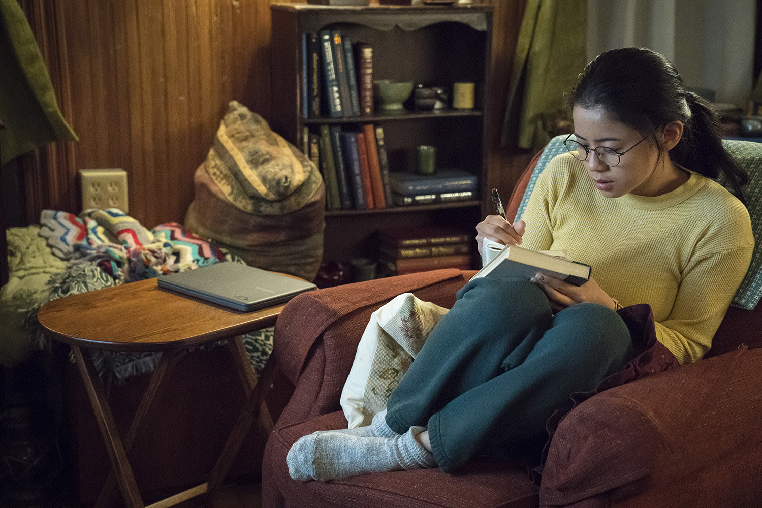 still image of leah lewis writing in a book for the movie the half of it