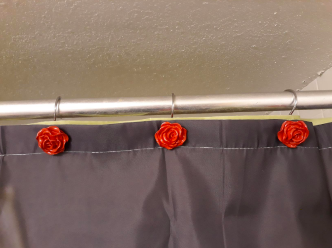 a reviewer photo of the rose shower curtain hooks