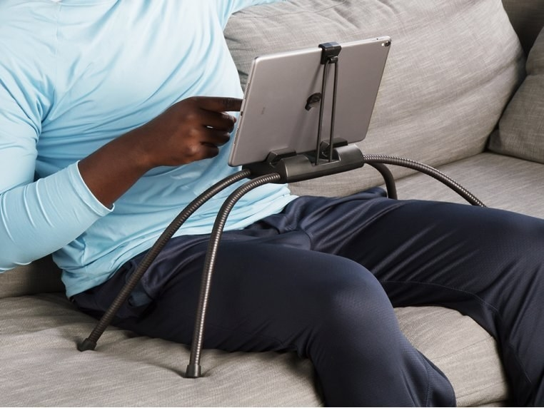 the black tablet holder with four legs over a model's legs, showing how it holds the tablet easily