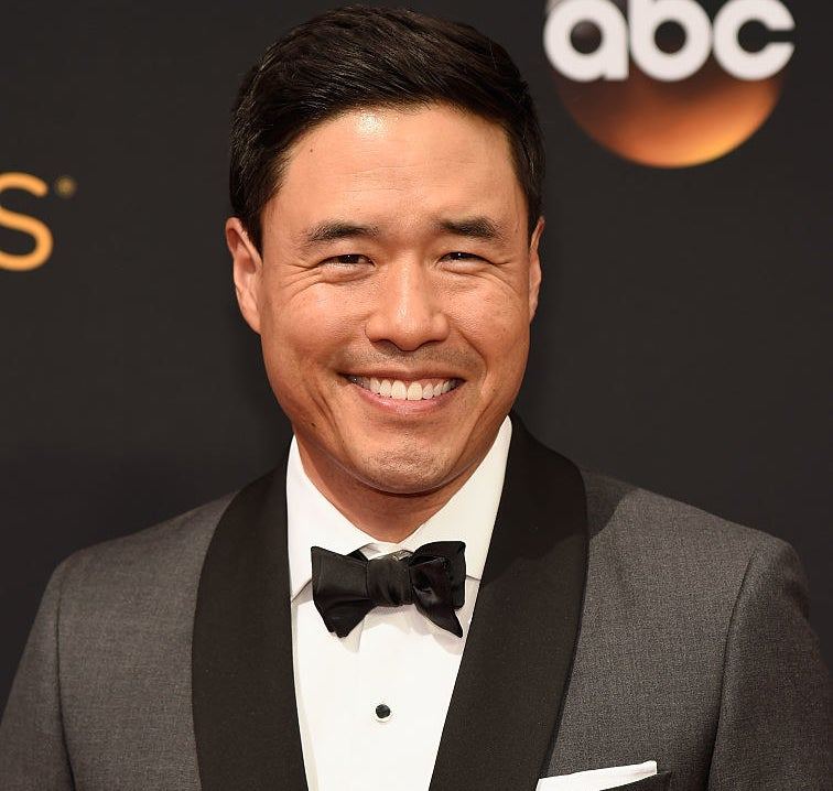 Randall Park wearing a suit and black bow tie at the Emmys red carpet