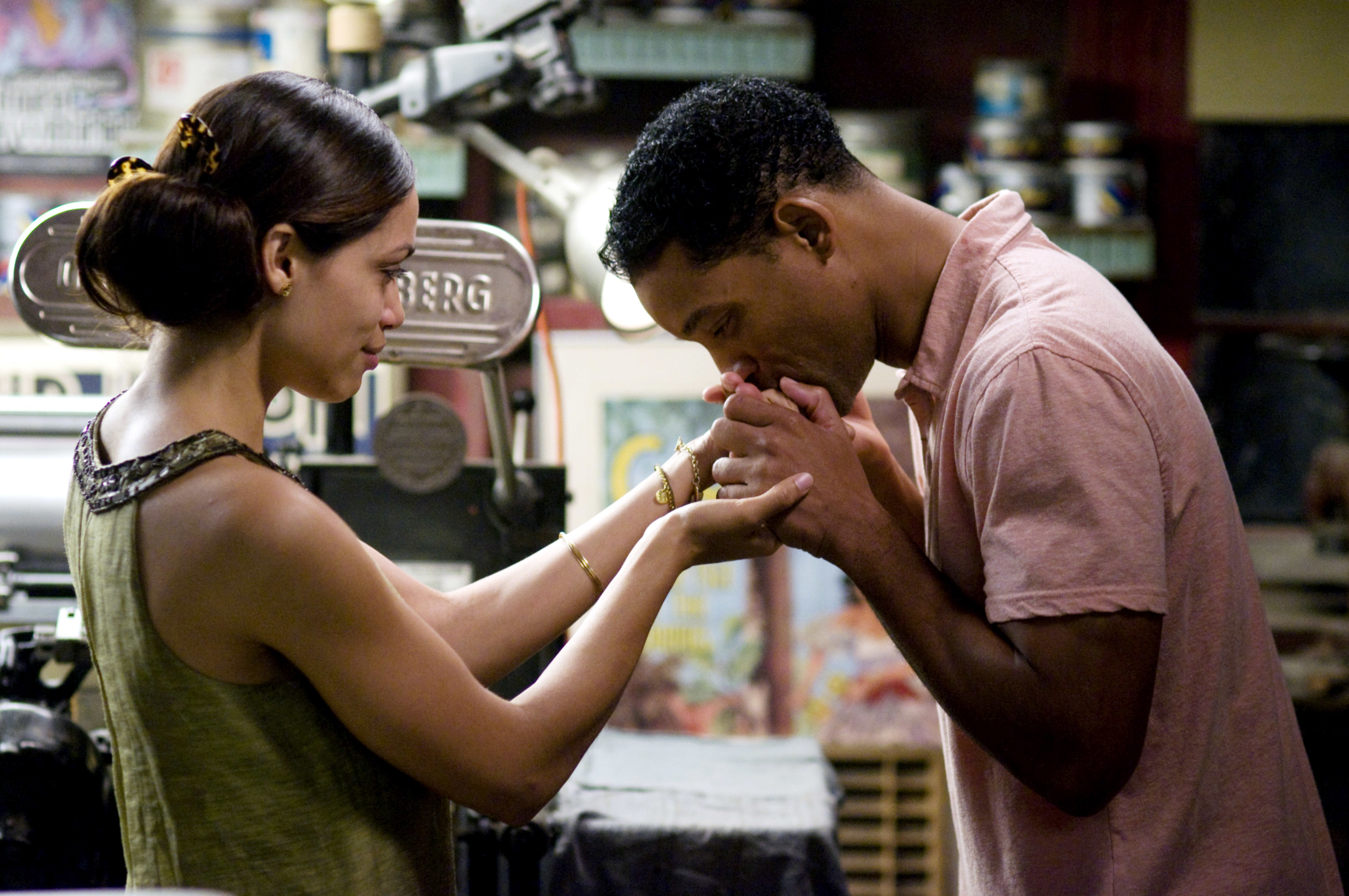 split image of rosario dawson and will smith in the movie seven pounds, will smith goes in to give roasrio dawson a kiss on the hand