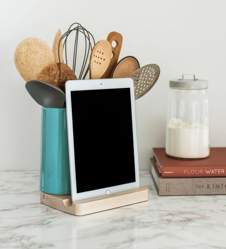 wood base tablet dock and green ceramic holder with kitchen utensils in it