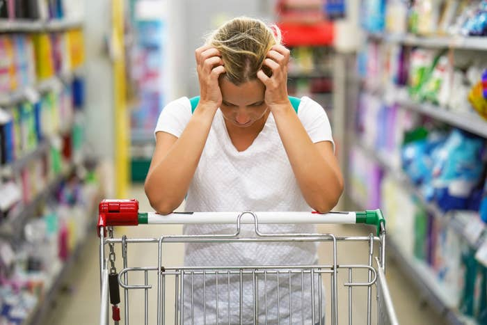 a stressed woman grocery shopping