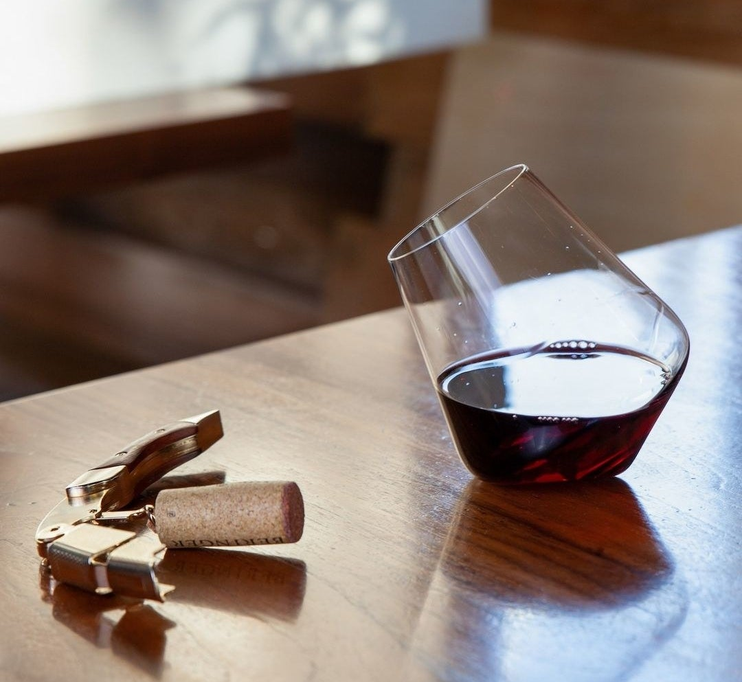 One of the wine glasses sitting on an angle on a tabletop