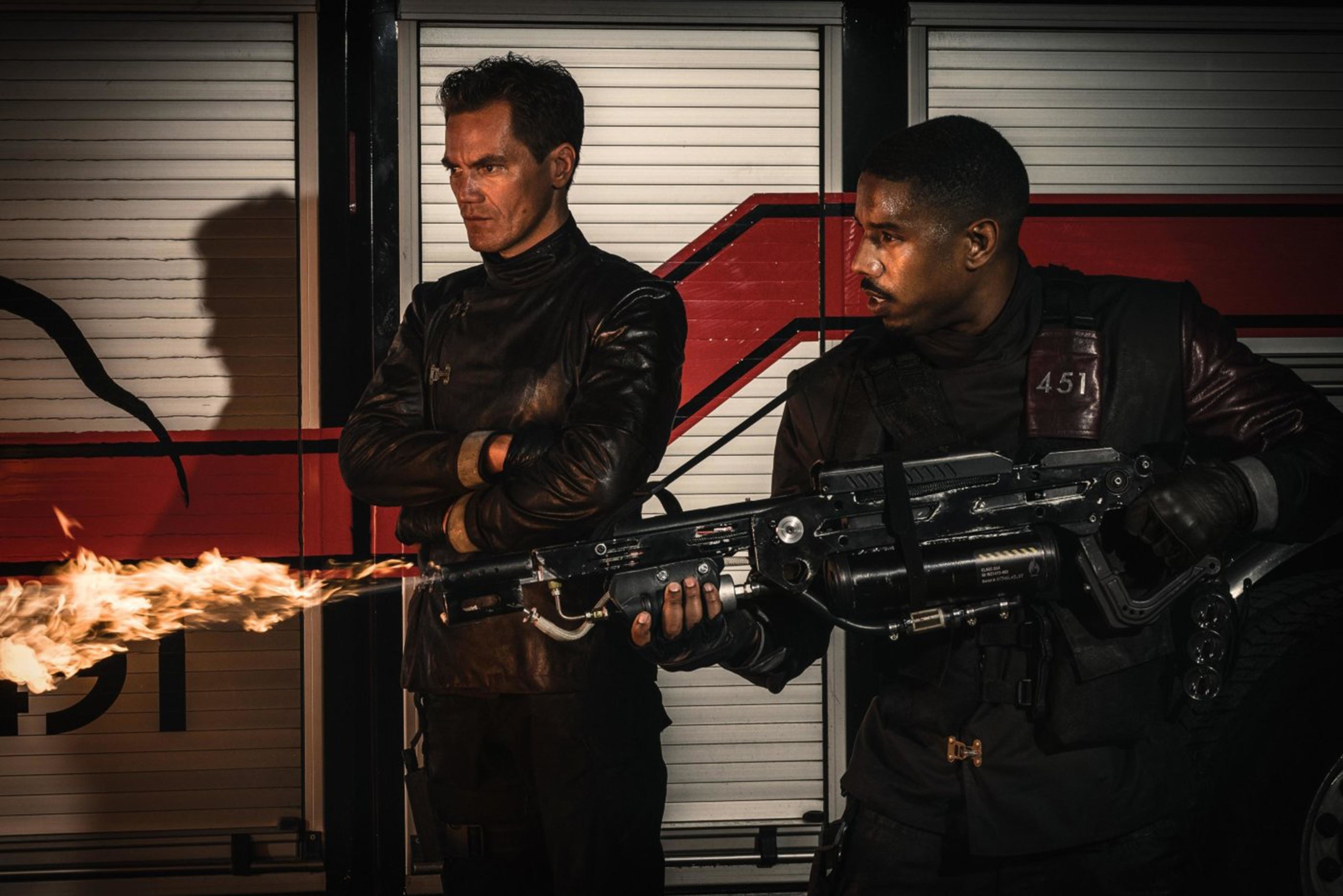 still image of michael shannon and michael b. jordan in the movie Fahrenheit 451, in the still michael b. jordan is holding a weapon that is releasing fire