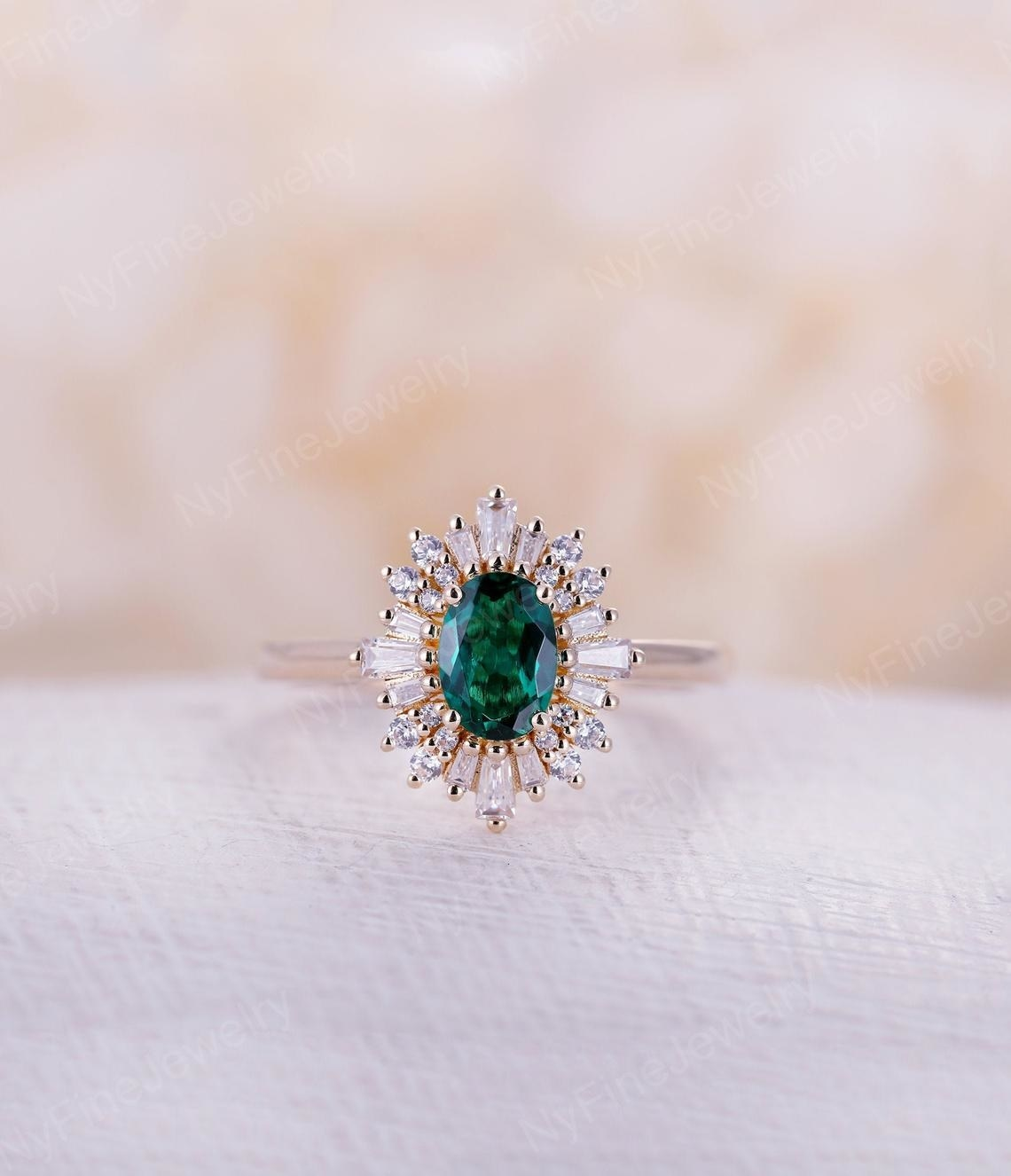 round emerald surrounded by baguette cut stones around the whole thing
