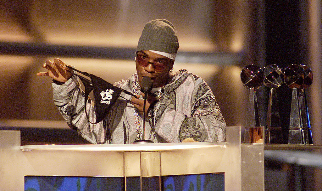 Sisqó onstage at an awards show and holding up a thong with his name on it