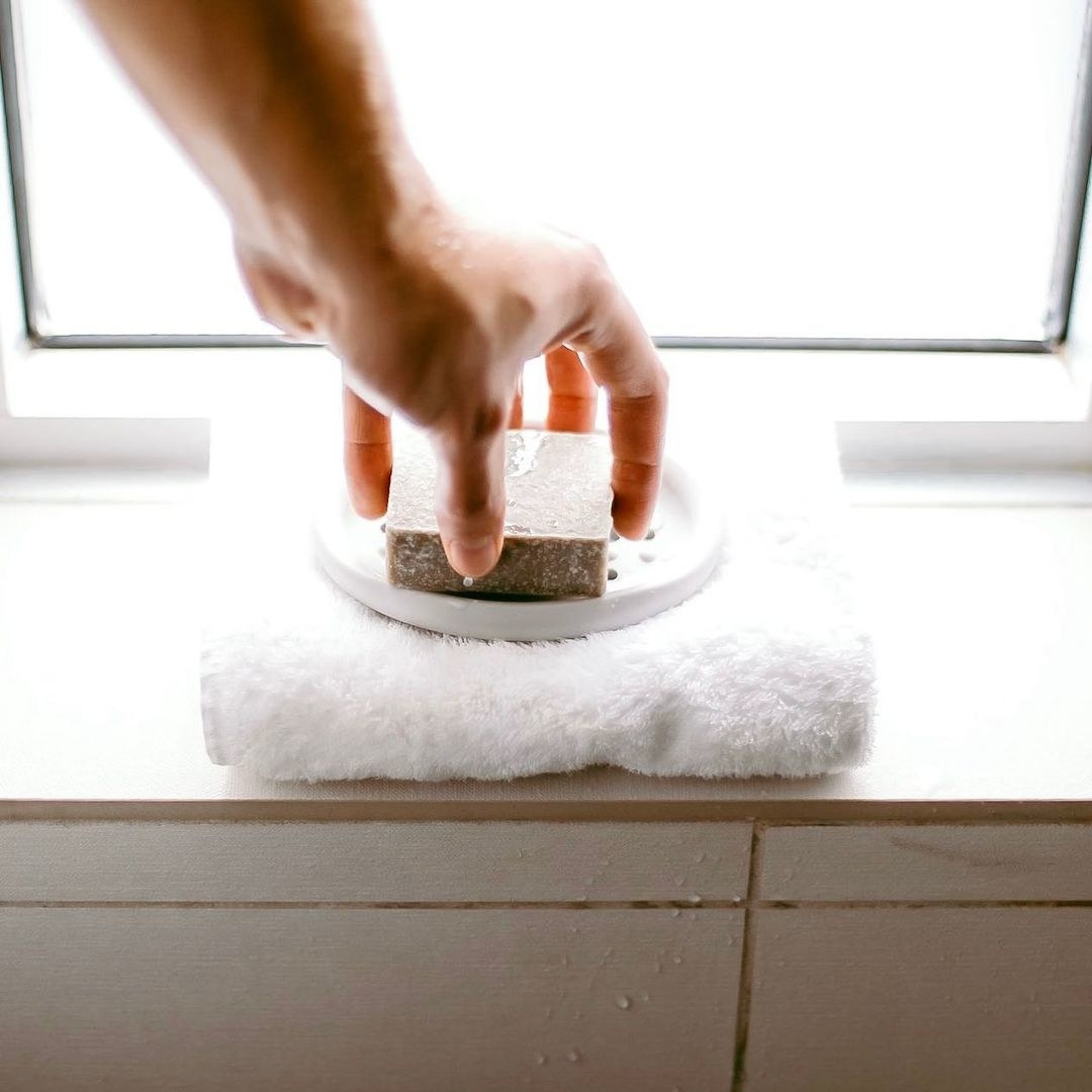 Someone putting sudsy soap onto the silicone soap dish