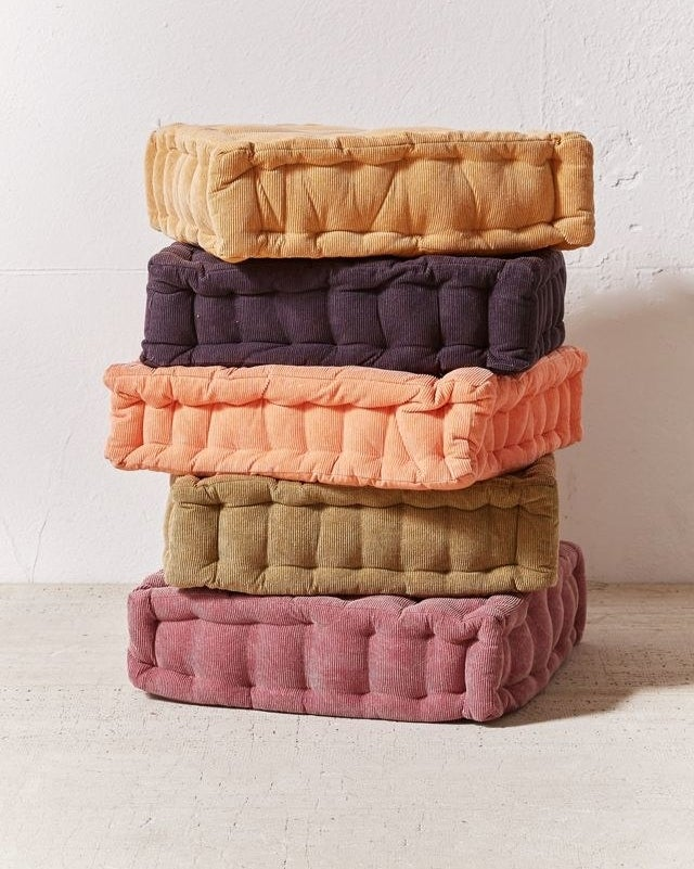 five different colored floor cushions stacked on top of each other