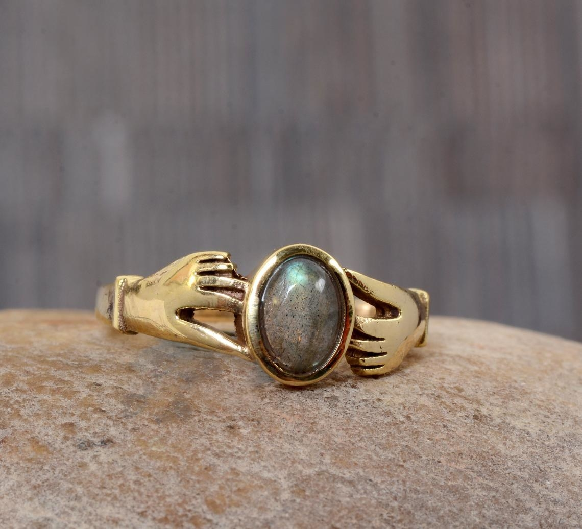 green and purple stone with gold ring shaped like two hands
