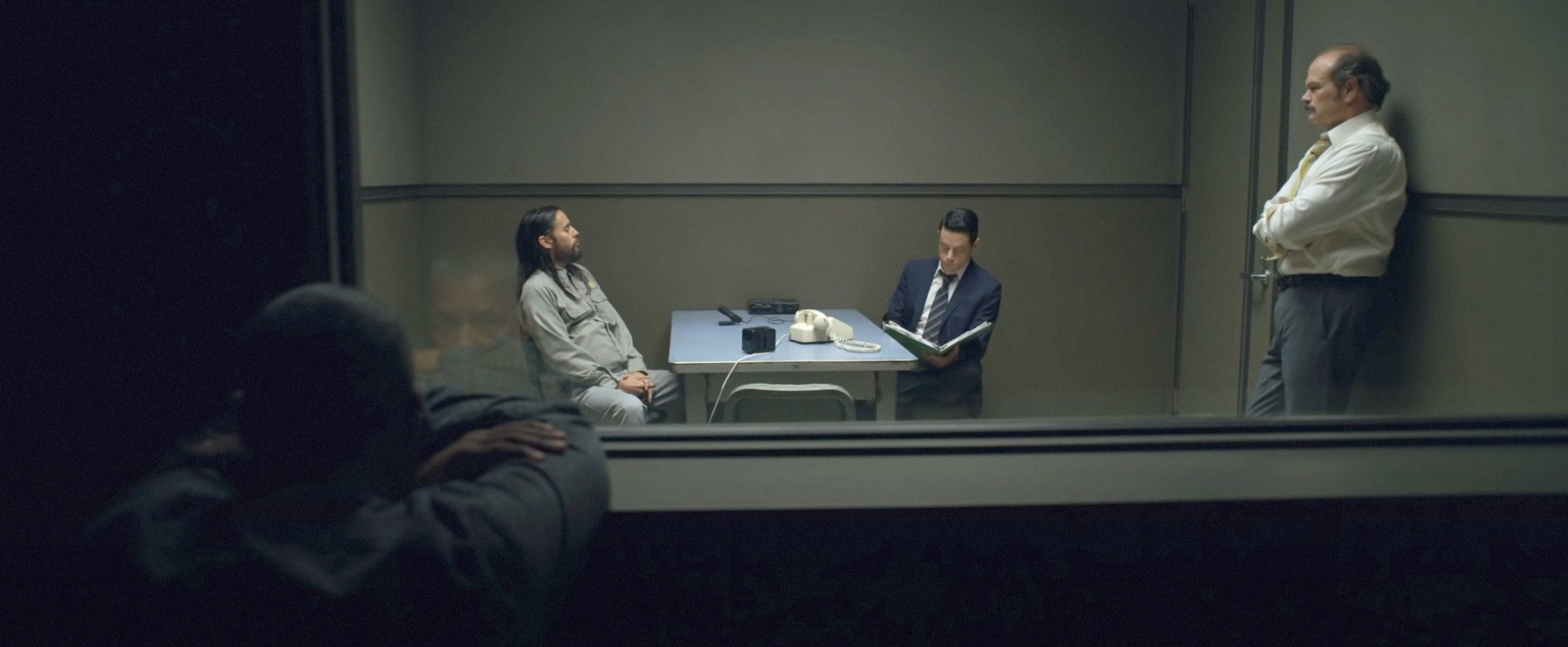 still image of denzel washington, jared leto, rami malek and chris bauer in the movie the little things, in the still jared leto is being questioned by rami malek inside of jail in a room