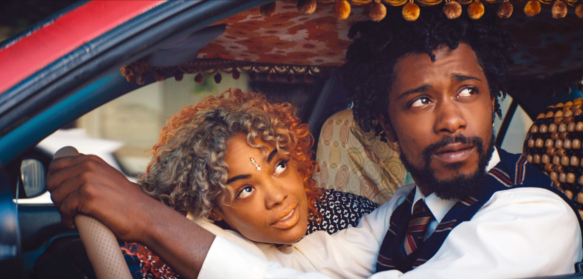 still image of tessa thompson and lakeith stanfield in the movie sorry to bother you, in the still is tessa and lakeith looking out their car window