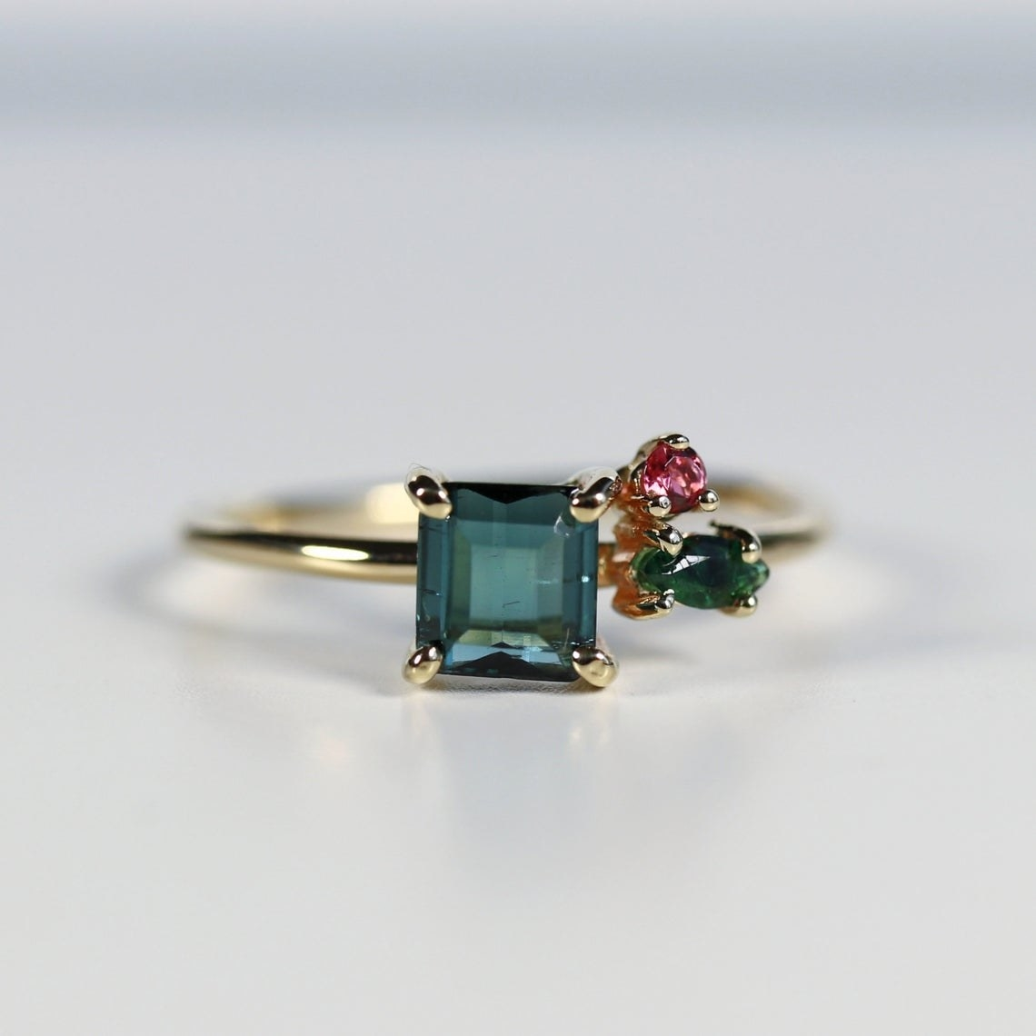 square green stone with pin and green teardrop stones on the right on simple gold band