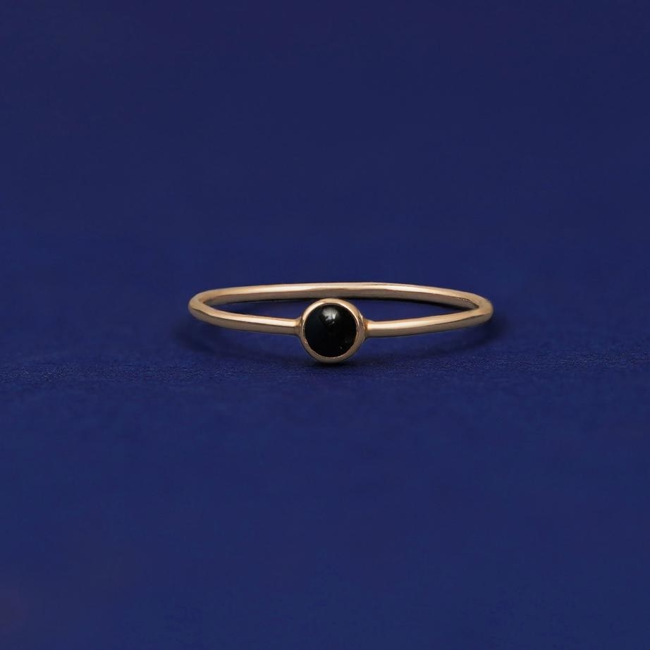 thin gold band with small round black stone