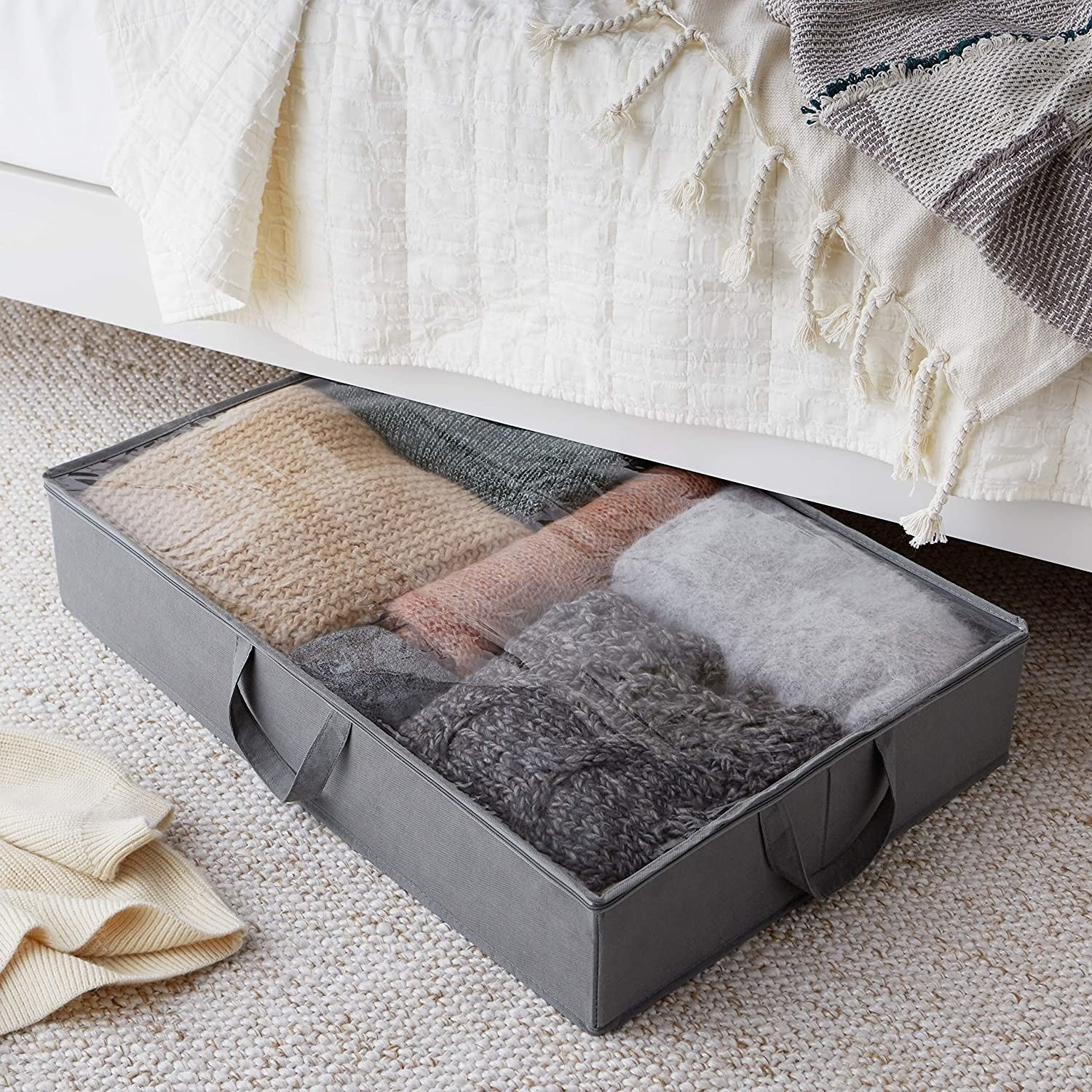 the bin with sweaters in it under a bed