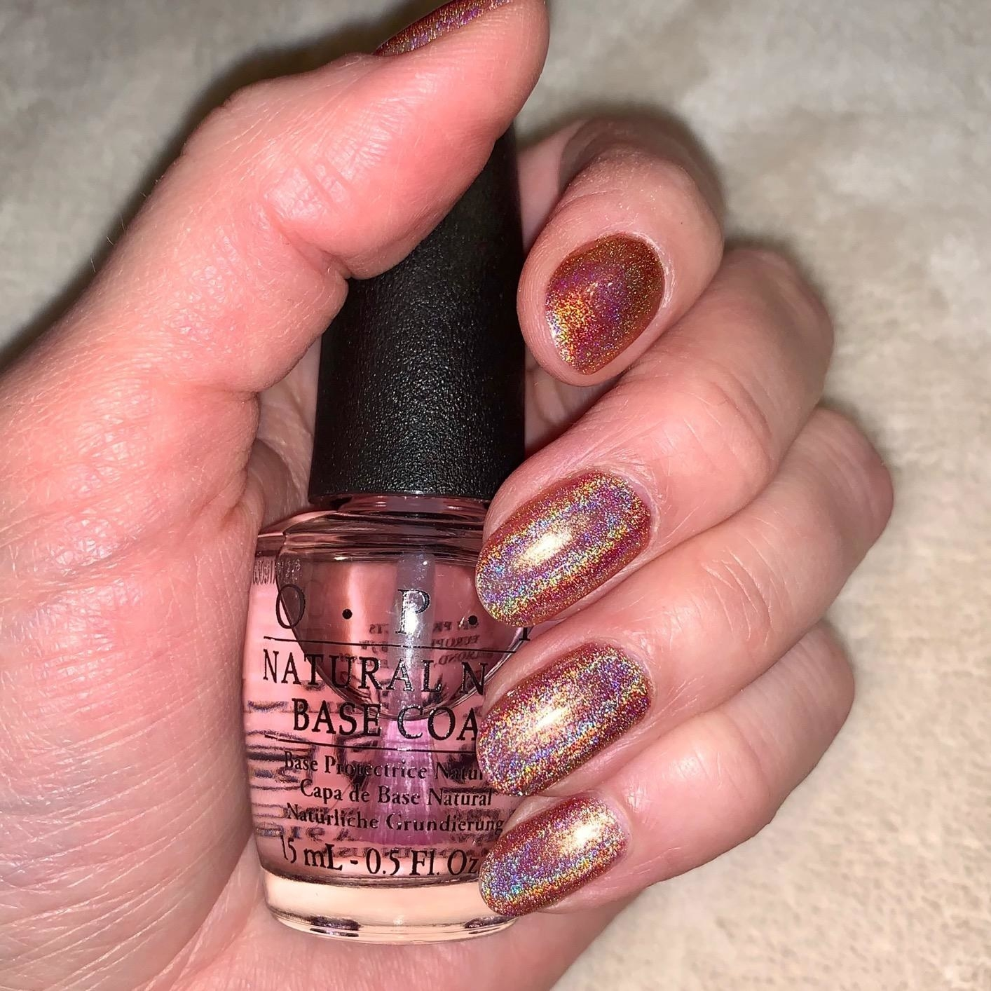 reviewer holding bottle of OPI Natural Nail Base Coat in hand with rose gold mani