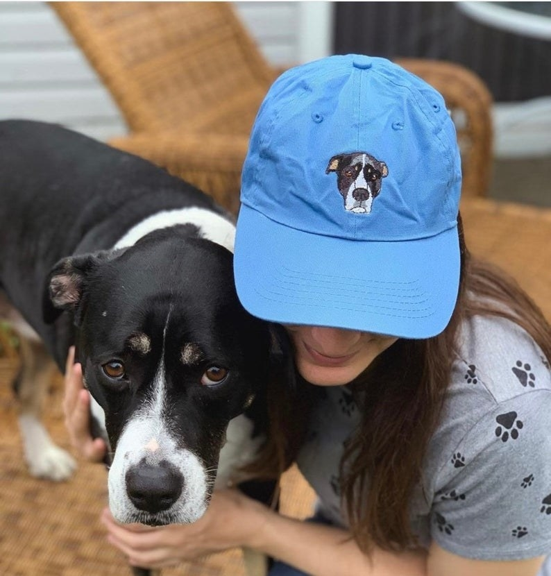 someone posing with their dog and wearing a blue baseball cap with their dog embroidered on it