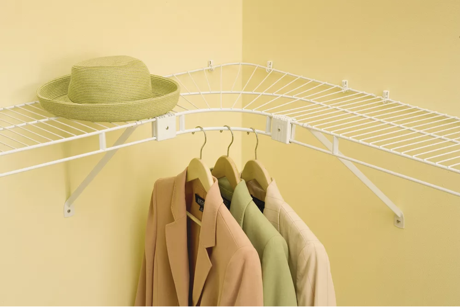 three coats hanging from the corner unit with one hat on the shelf