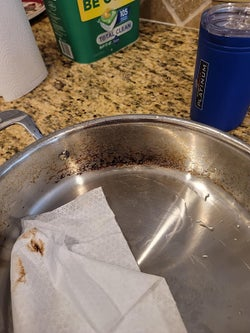 a pan being cleaned with the towel