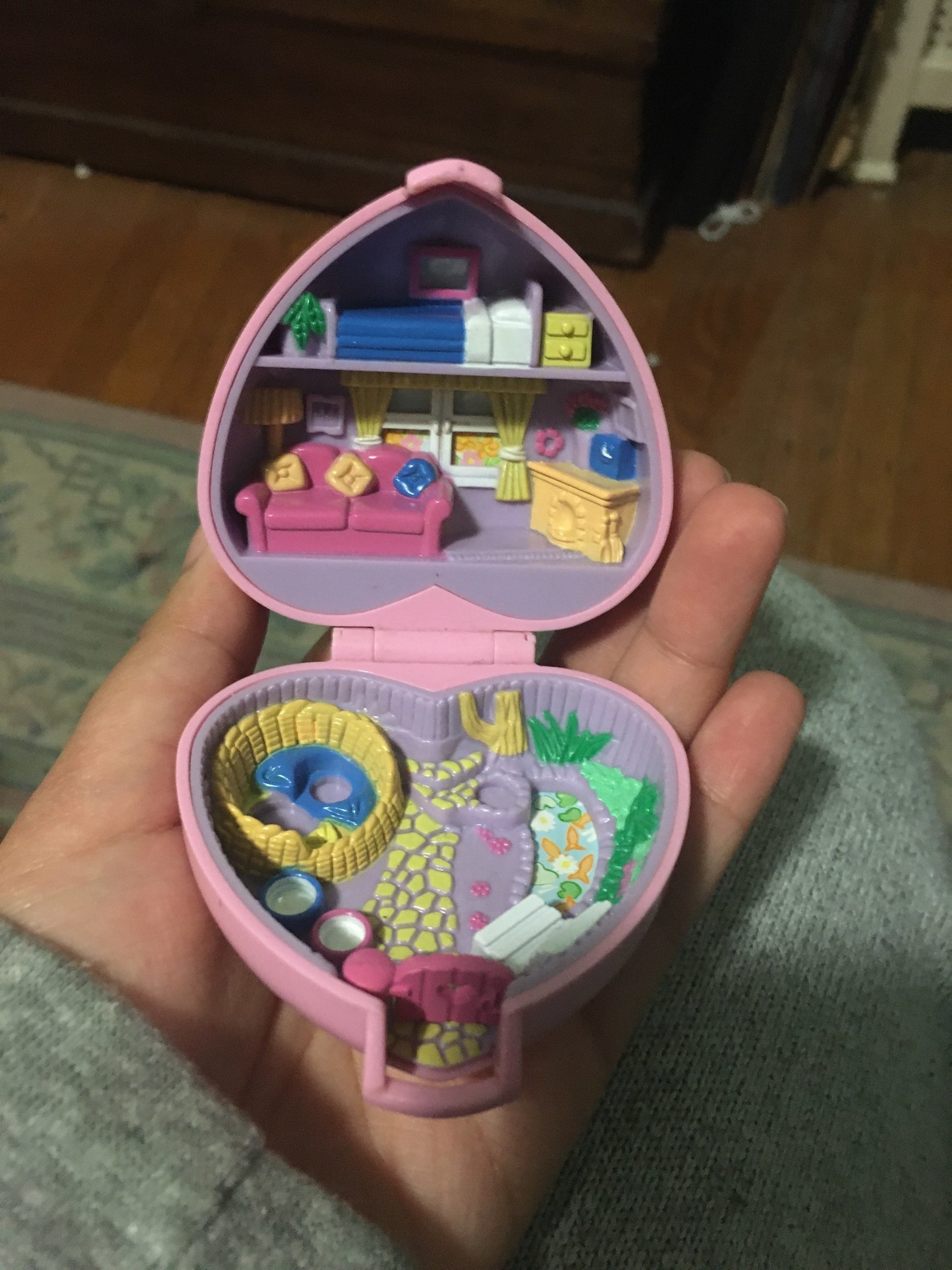 A heart shaped Polly Pocket with a bedroom and living room in the top compartment and a garden in the bottom
