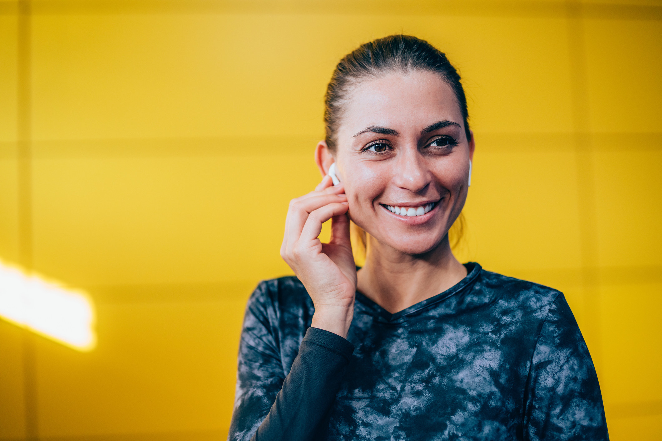 A woman smiling and putting her AirPod in