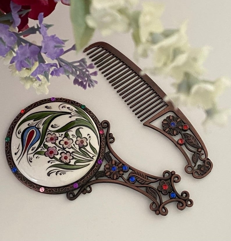 A handheld mirror and comb on a table by some flowers