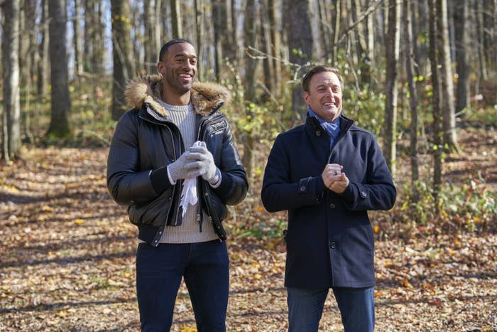 Matt James and Chris Harrison stand next to each other in the woods in an episode of The Bachelor