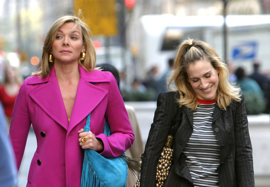"Kim Cattrall and Sarah Jessica Parker walk down the street during a scene in ""Sex And The City"""