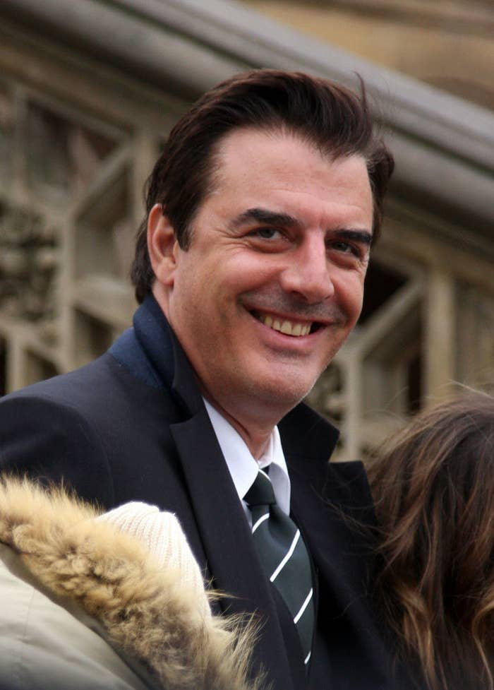 "Actor Chris Noth smiling in a suit and tie on location for a Vogue ""Sex and the City"" photo shoot"