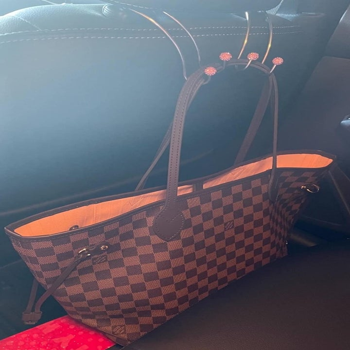 reviewer photo showing their large purse hanging from the hooks behind the driver's seat of their car