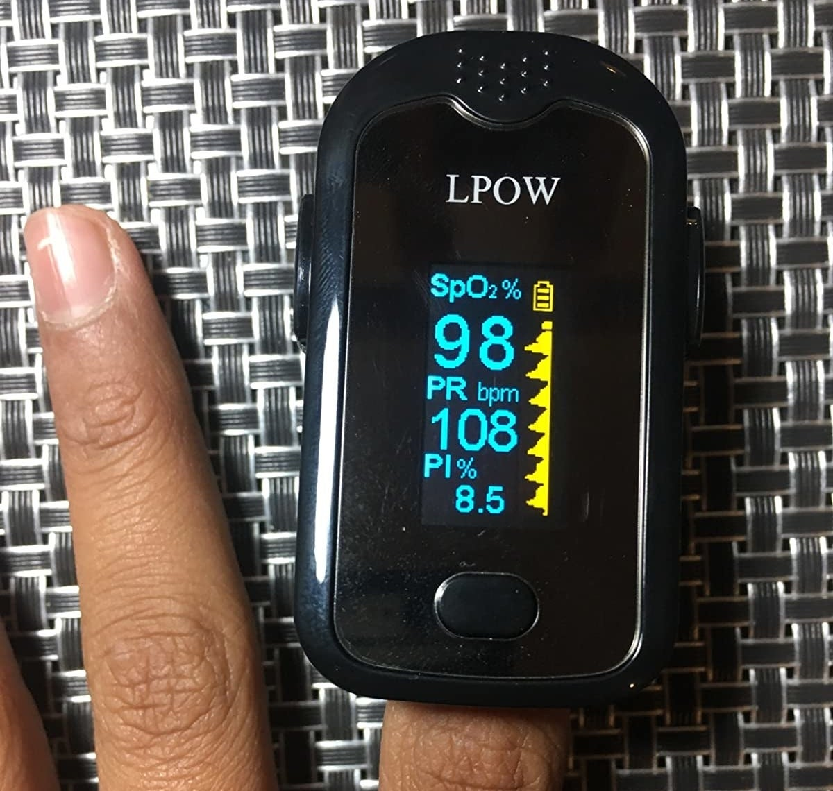 reviewer showing the pulse oximeter on their index finger