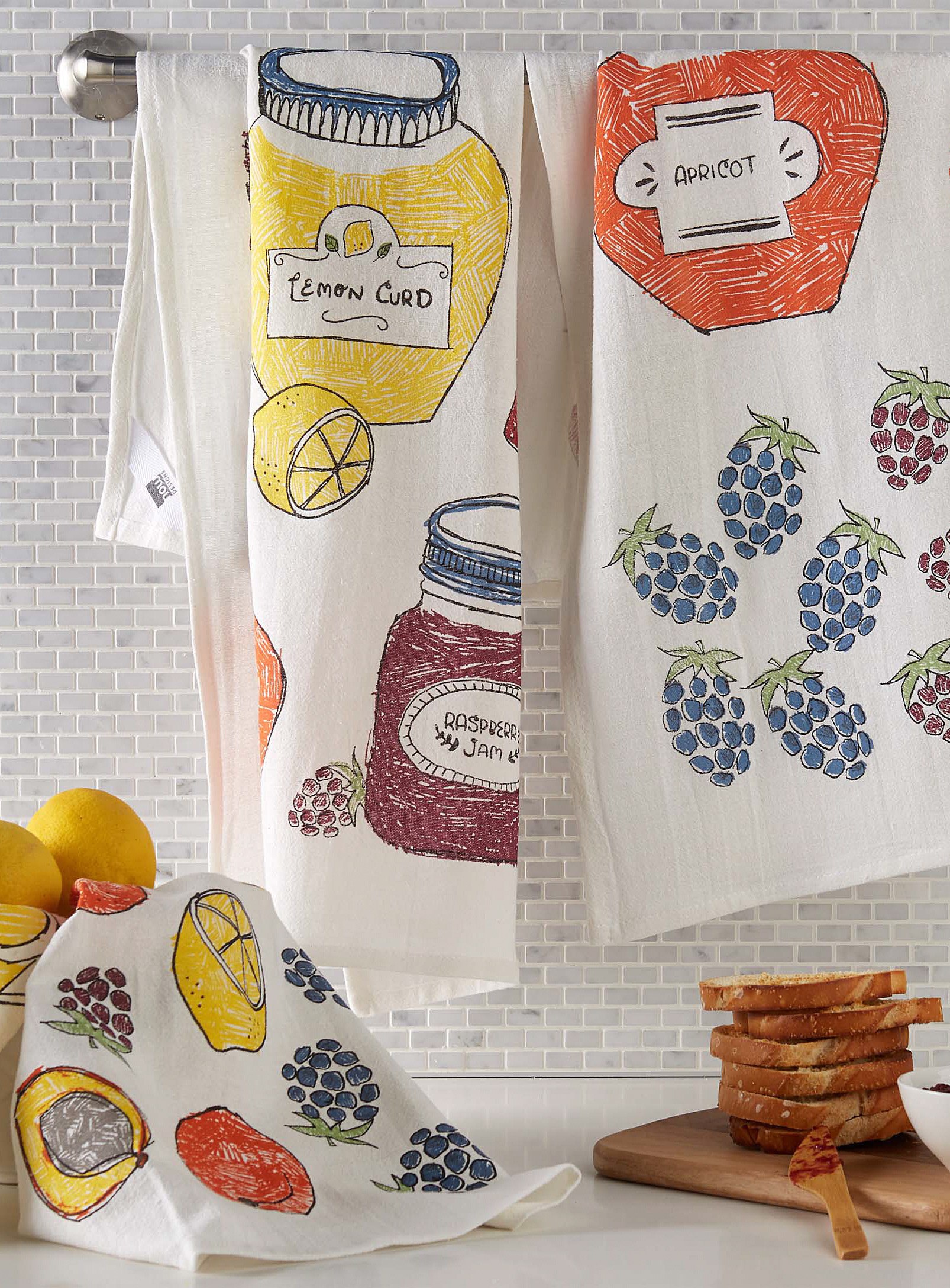 Two tea towels hanging on a bar above a kitchen counter