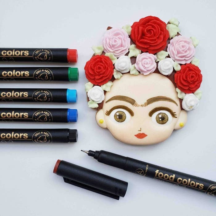 A bunch of markers next to a cookie that looks like Frida Kahlo