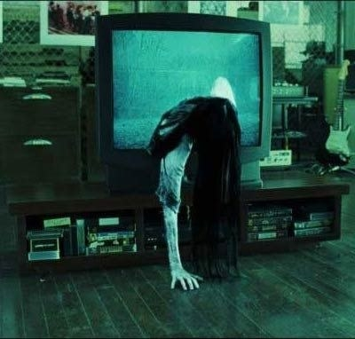 A scary girl coming through a haunted TV