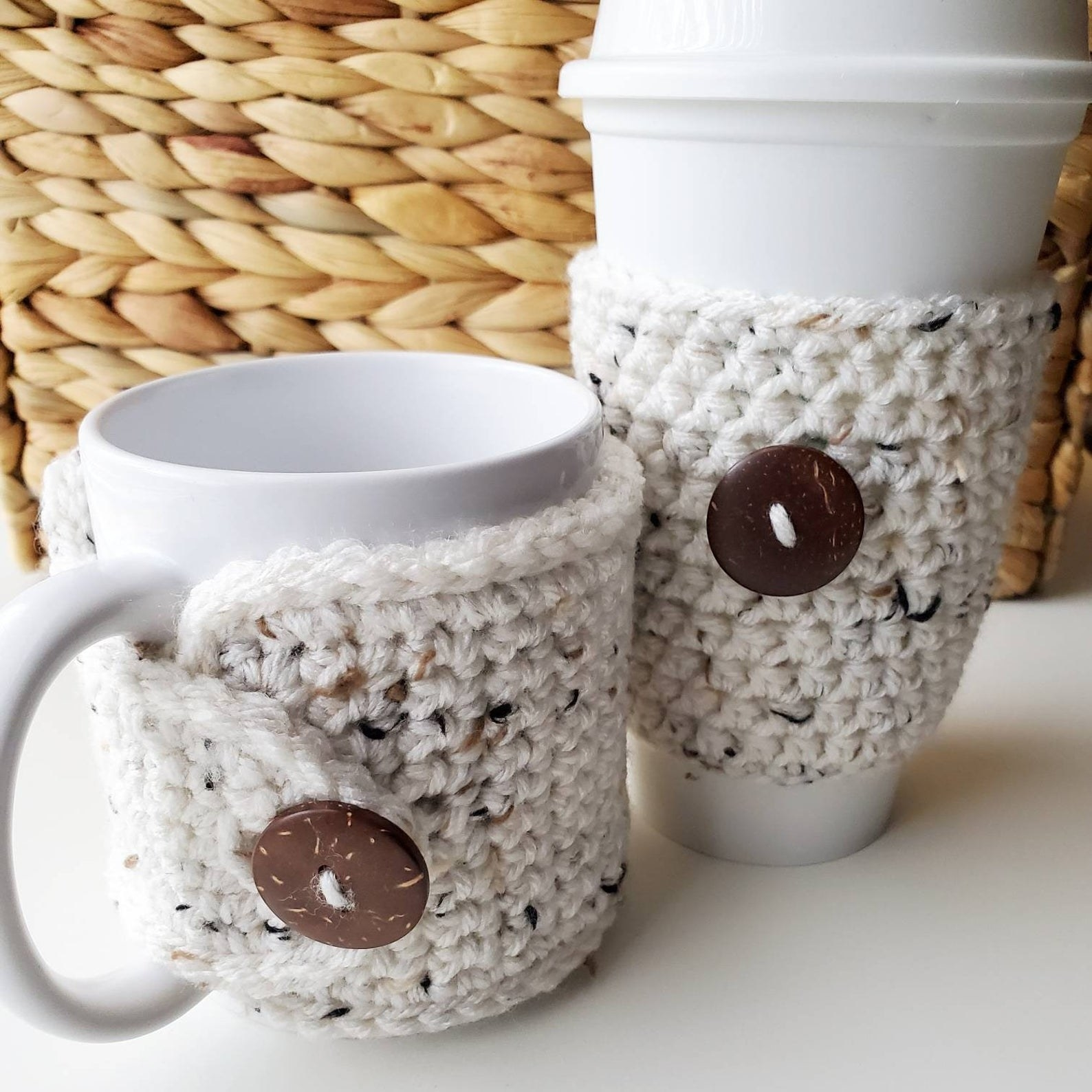 The two oatmeal koozies that are fastened by a button and wrapped around a mug and travel coffee cup