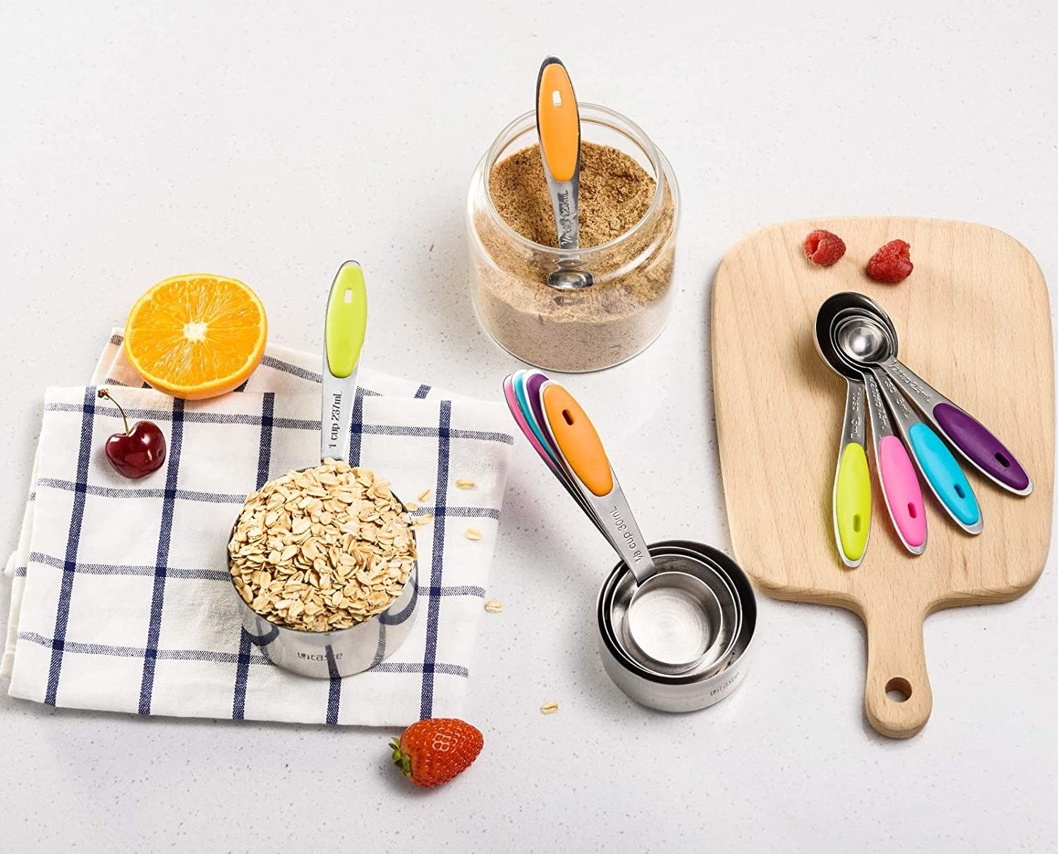 A set of measuring spoons on a wooden cutting board next to a stack of measuring cups
