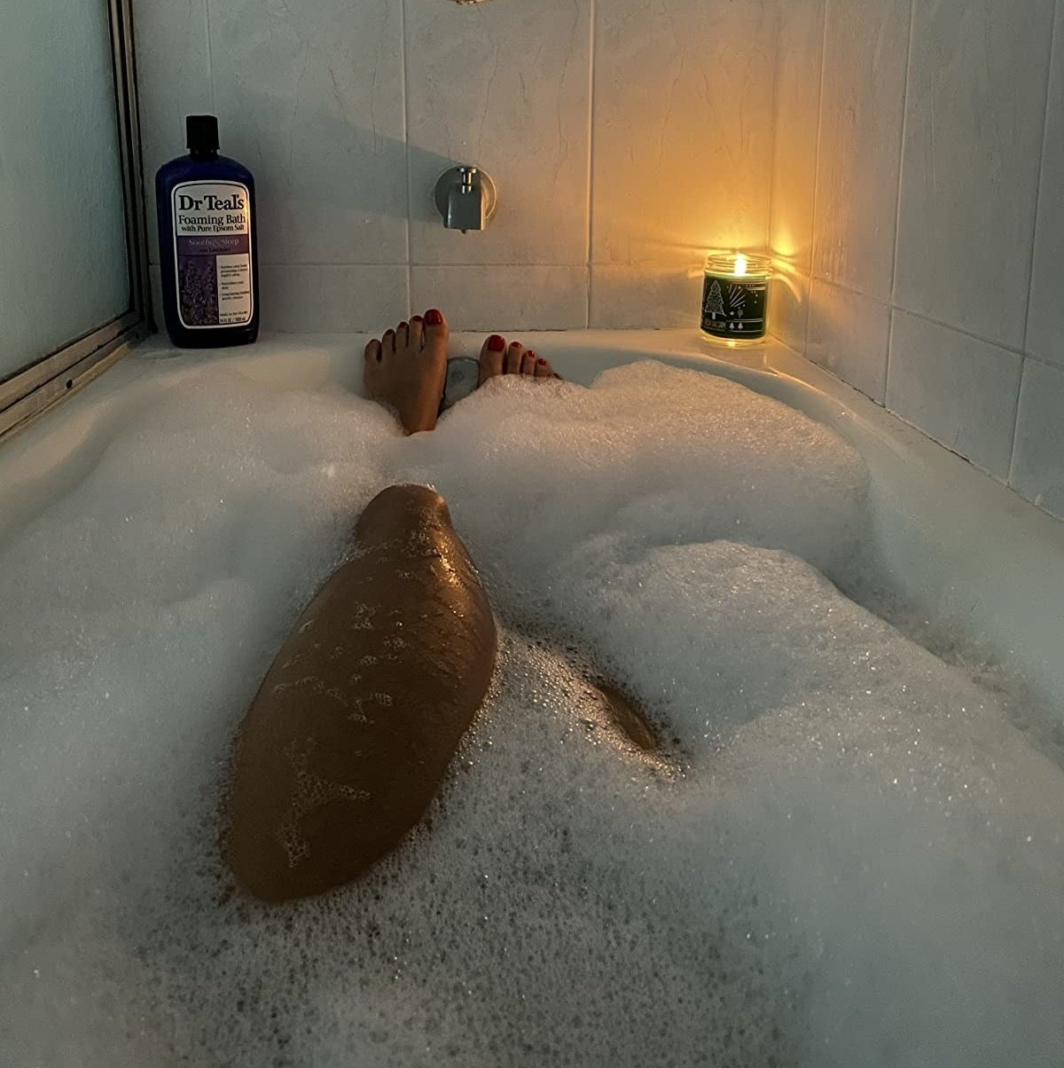 Reviewer in a bubble bath with a bottle of Dr Teal's on display on the edge of the tub