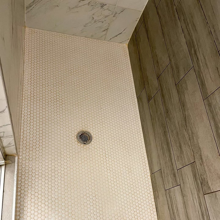 same reviewer showing their shower looking brand new after using the tile cleaner