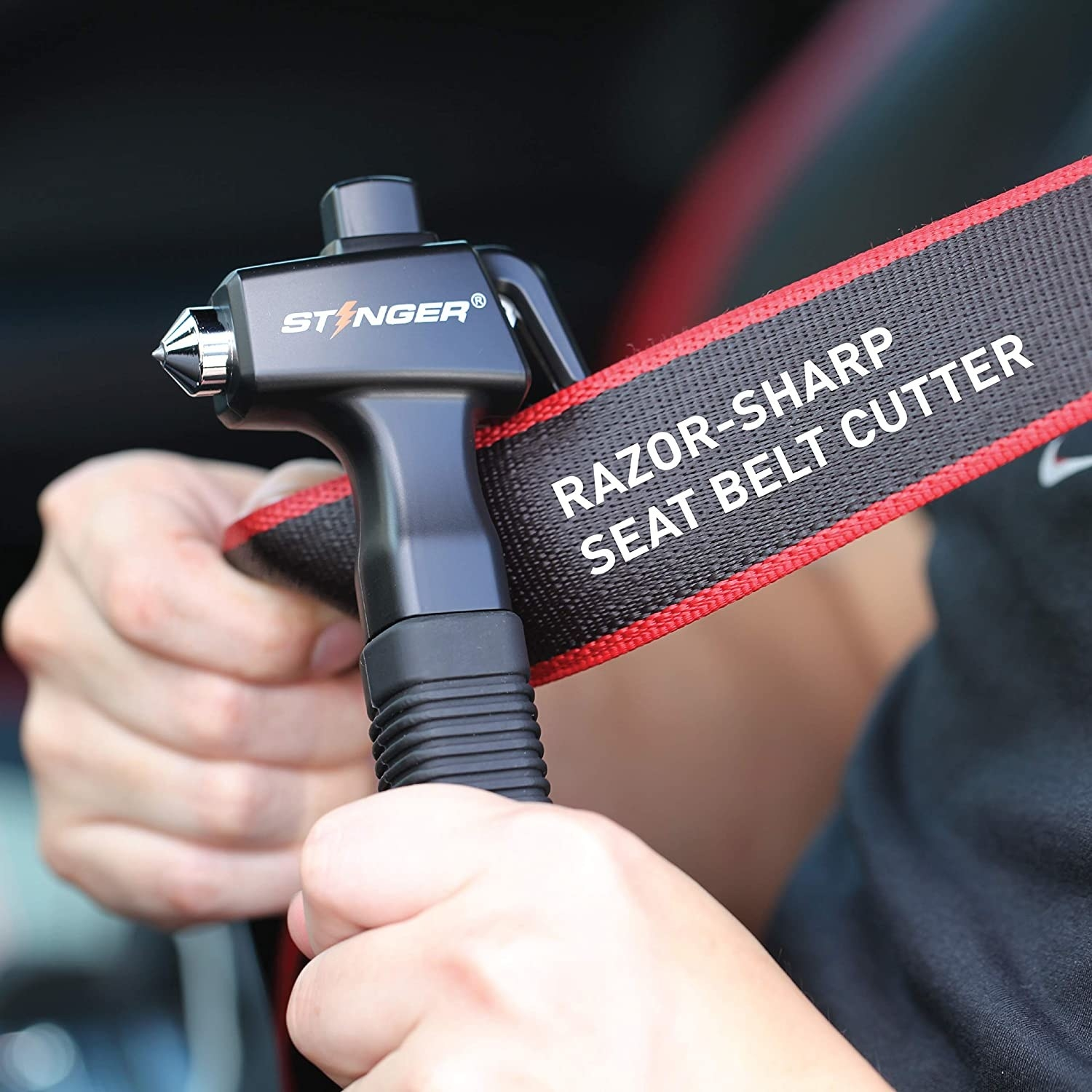 person cutting their seat belt with the device