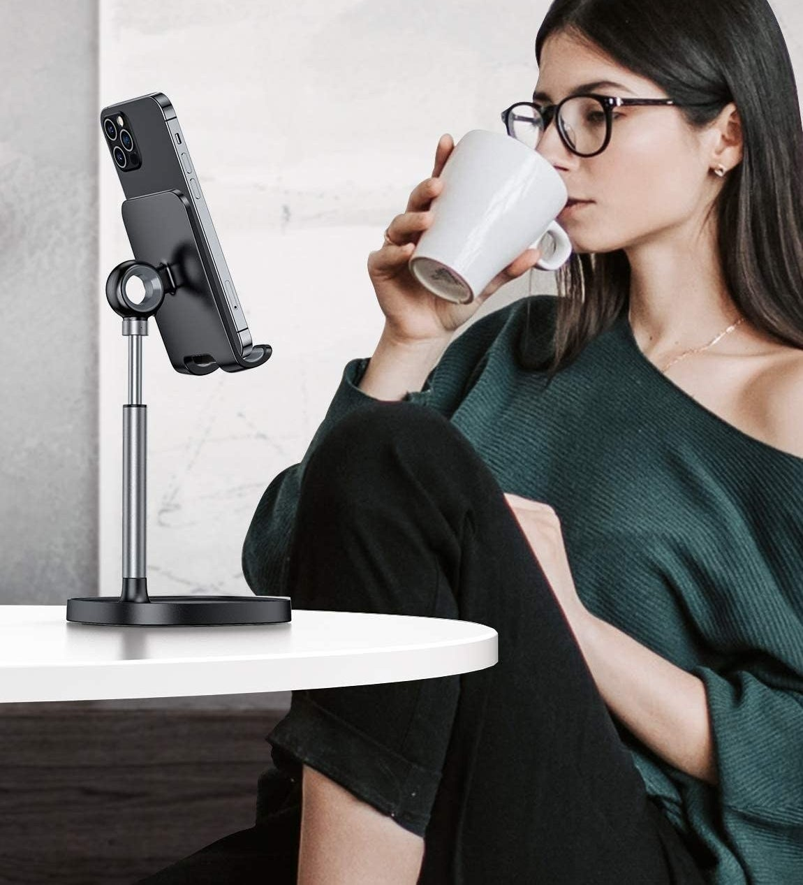 A model watching something on their phone which is propped up to eye level on a black stand on a desk