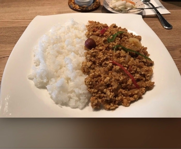 A plate filled with half white rice and half minced meat, brown curry