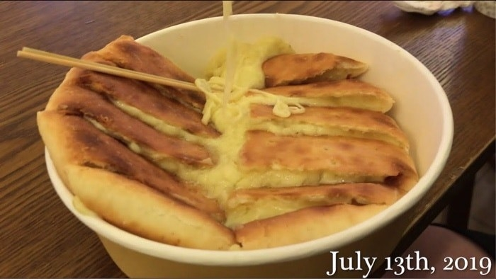 A bowl holds a sliced, crispy pancake oozing with cheese