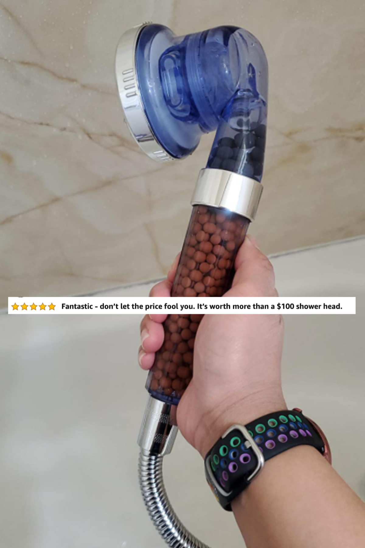reviewer holding shower head with a review image on top saying it's worth more money