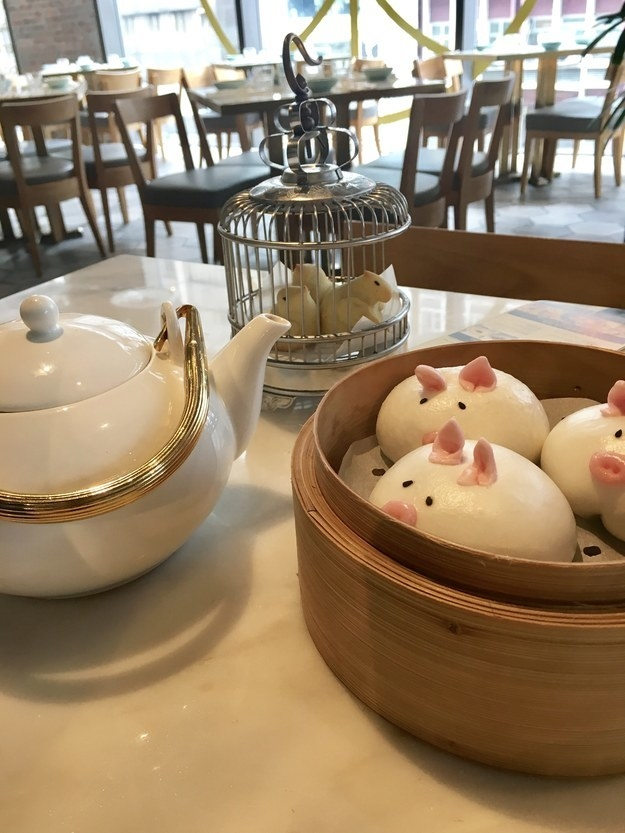 A table holds a teapot and a bamboo steamer with bao shaped like pigs