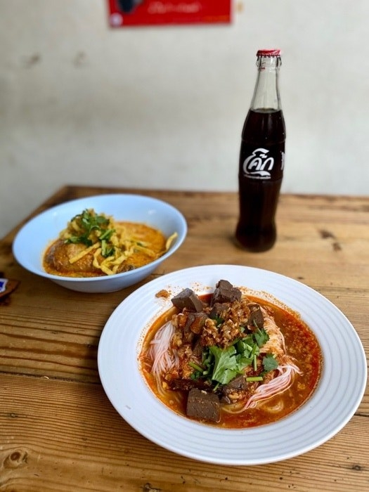 A table holds two dishes of curry noodles with meat