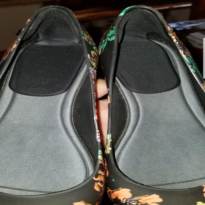 A reviewer photo of a pair of shoes with black heel inserts inside
