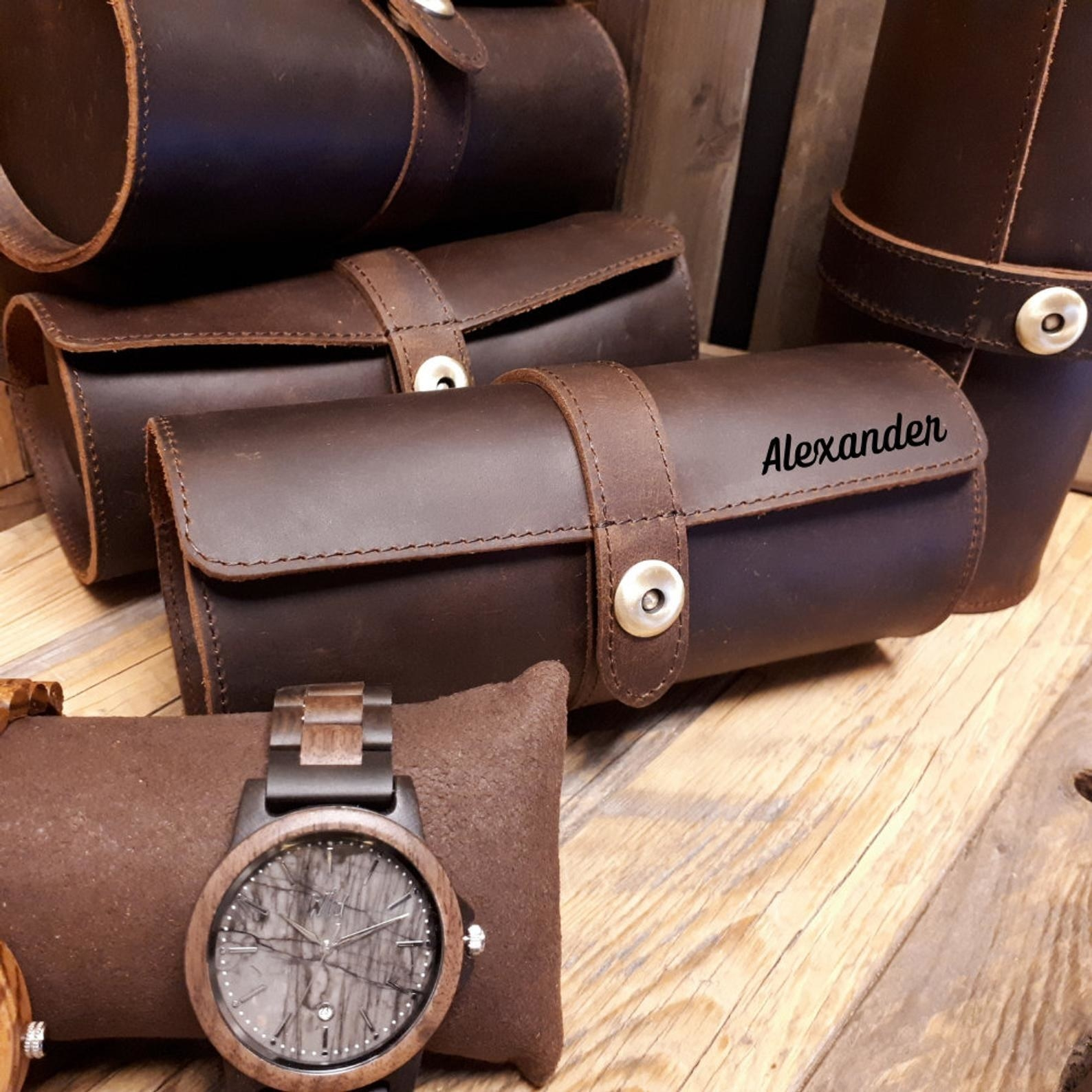 A brown leather watch roll case with a snap closure