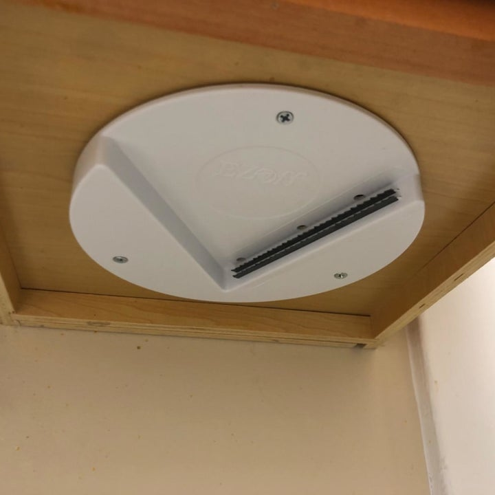 A reviewer photo of the lid opener mounted under the cabinet