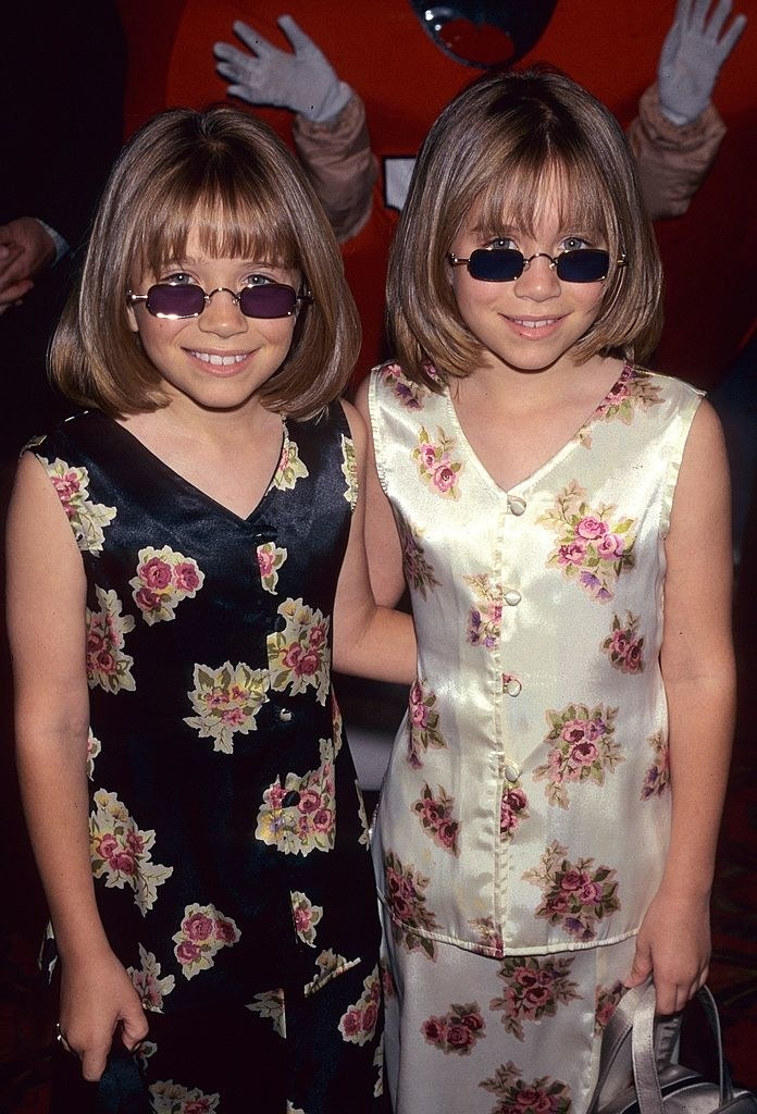 A young Mary-Kate and Ashley wearing matching satin tops and skirts with a floral print and sunglasses
